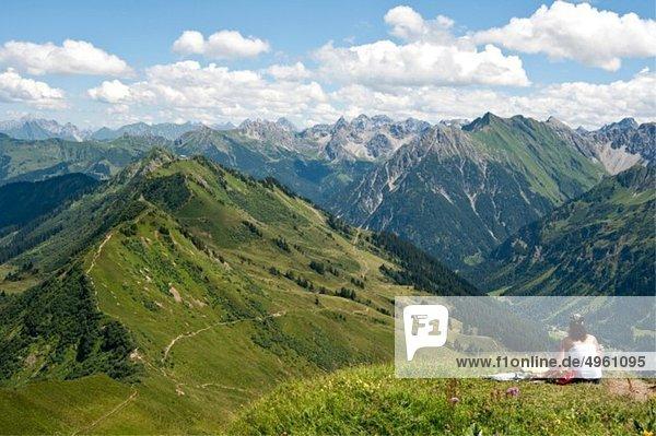 Österreich  Vorarlberg  Frau sitzend bei Blickrichtung