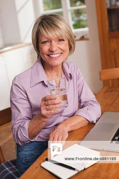 Seniorin mit Wasserglas und Laptop,  lächelnd,  Portrait