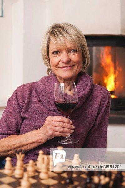 Seniorin mit Weinglas und Schachbrett im Vordergrund