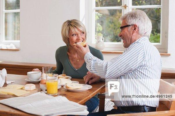 Älterer Mann füttert Frühstück an ältere Frau