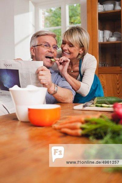 Senior Frau füttert Gurkenscheibe an Senior Mann