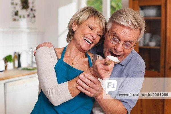 Ältere Frau füttert älteren Mann