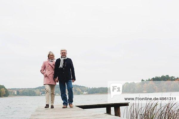 Deutschland  Kratzeburg  Seniorenpaar auf Strandpromenade  lächelnd  Portrait