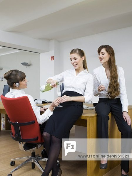 Junge Frauen genießen Sekt im Büro