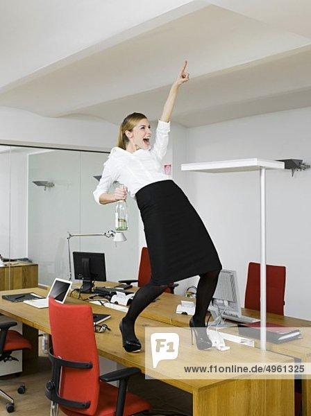 Junge Frau mit Sekt auf dem Tisch im Büro