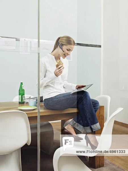 Junge Frau beim Betrachten des digitalen Tabletts