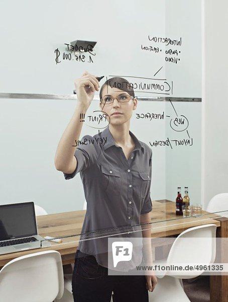 Junge Frau schreibt auf Glasfenster