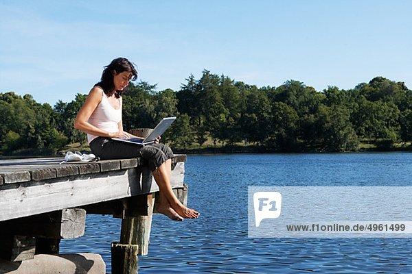 Eine Frau mit einem Laptop auf einer Mole an einem See  Schweden.
