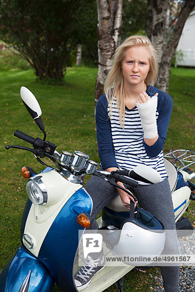 Teenage girl with bandage on hand sitting on scooter