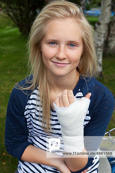 Teenage girl with bandage on hand  smiling  portrait