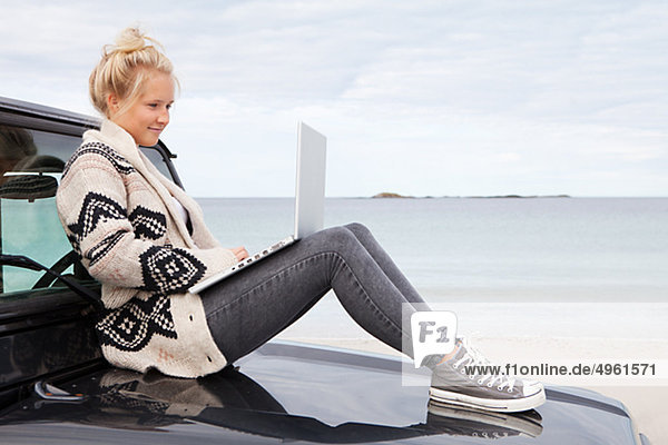 Teenage girl sitting on off road vehicle  using laptop