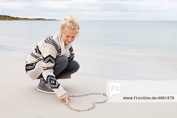 Teenagerin machen Herzform auf sand