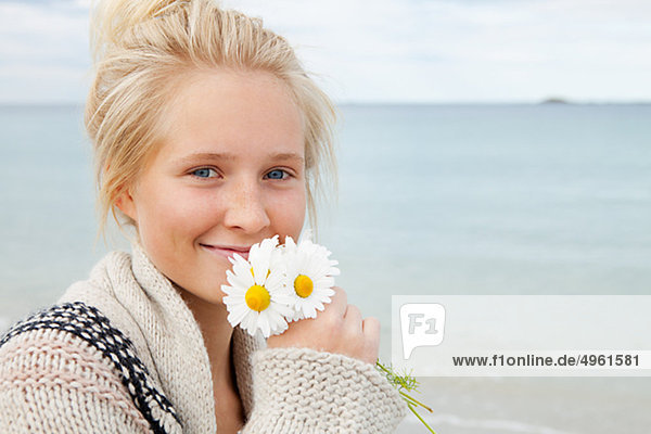 Teenage girl holding flowers  smiling  portrait