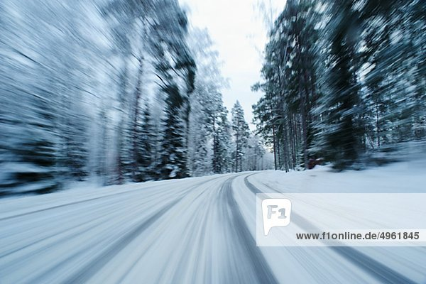 Blurred motion view of snow covered country road