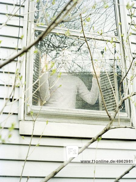 Person  die aus dem Fenster schaut