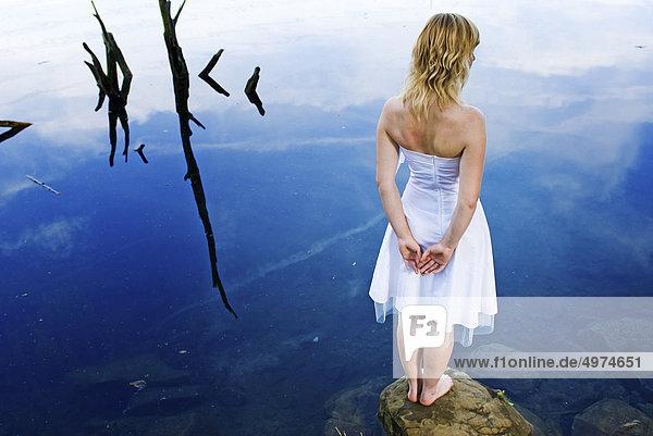 Junge blonde Frau in weißem Kleid an einem See