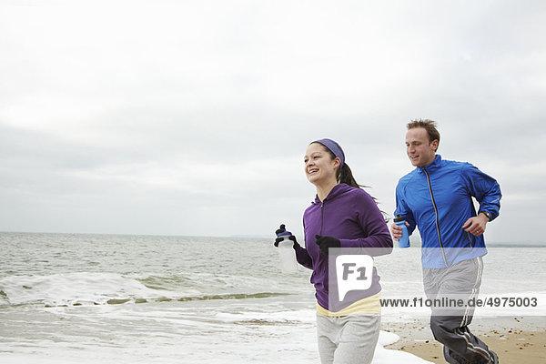 Paar läuft am Strand bei bewölktem Himmel