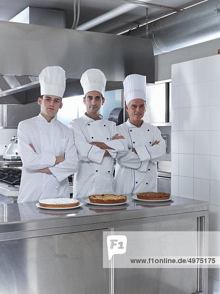 Drei Generationen von Köchen in der Restaurantküche mit hausgemachtem Kuchen