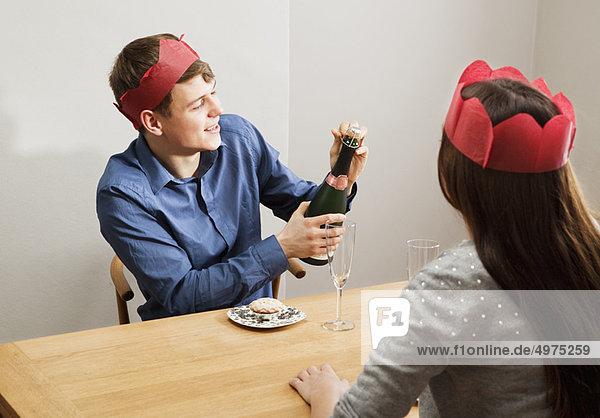 Junger Mann öffnet Champagnerflasche