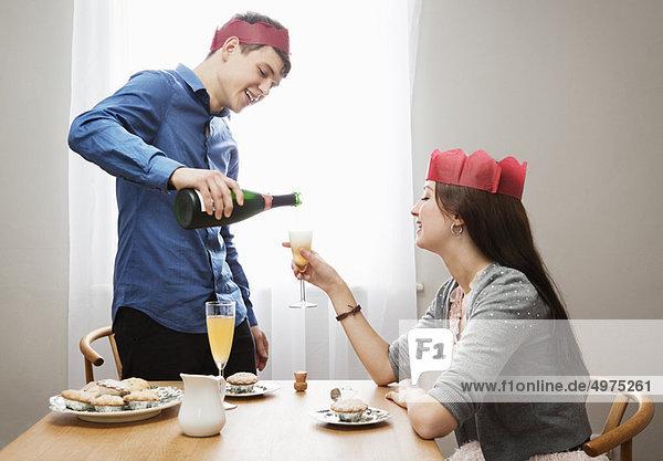 Mann poors Champagner im Frauenglas
