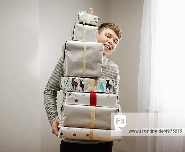 Mann hält einen Haufen Weihnachtsgeschenke.
