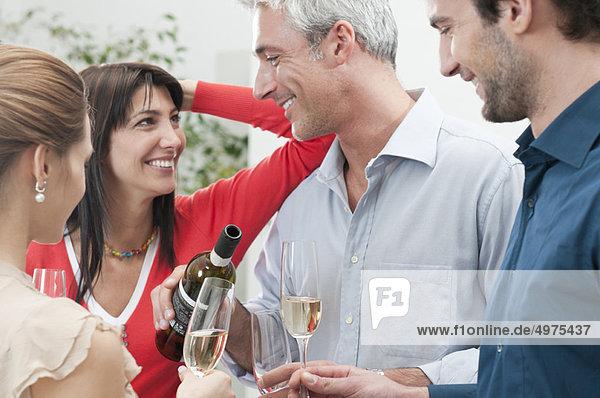 Glückliche lächelnde Freunde trinken Wein