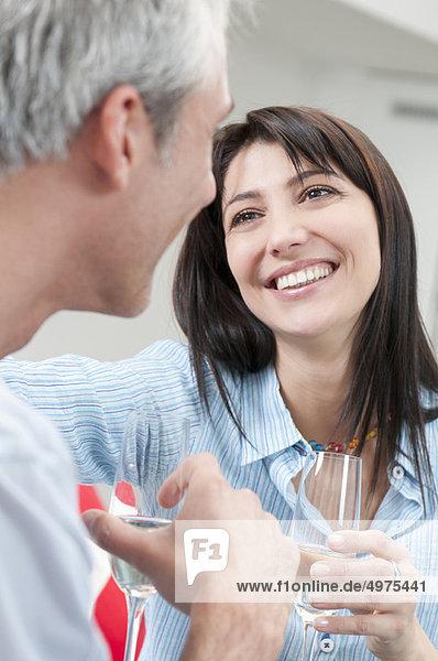 Glückliches Paar trinkt Weißwein