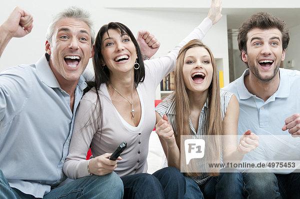 Aufgeregte Freunde beim Sport im Fernsehen