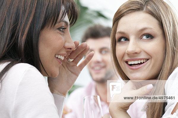 Mädchen flüstern ein Geheimnis