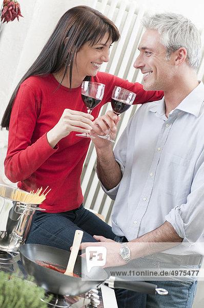 Paar trinkt Wein beim Kochen