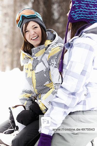Teenager-Mädchen in Snowboardausrüstung lächelnd
