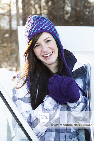 Teen girl by car in winter