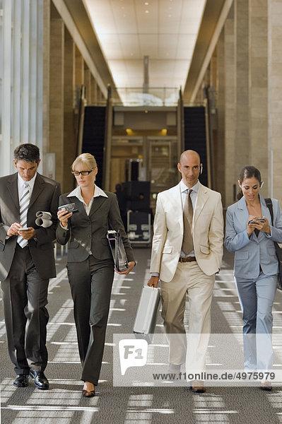 Geschäftsleute  die einen Korridor entlang gehen.