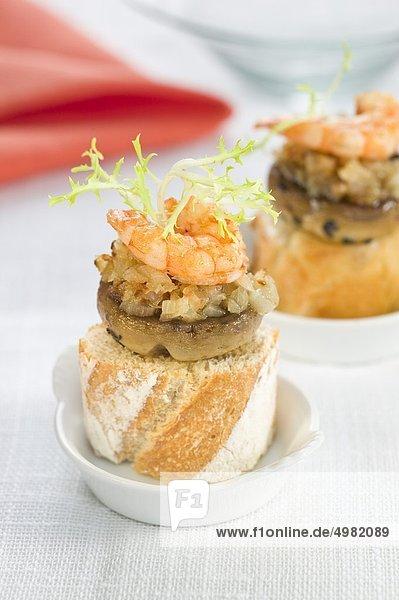 Pilze  Garnelen und Zwiebel auf eine mundgerechte Scheibe Brot