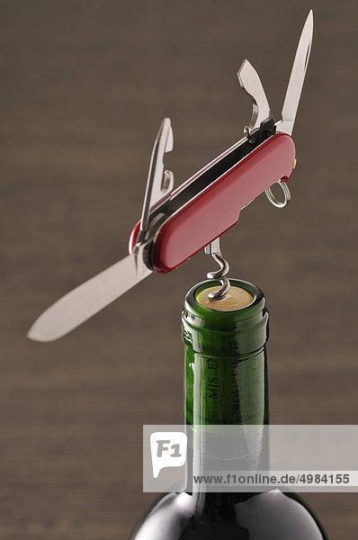 Openning eine Flasche Wein mit einem Korkenzieher auf ein Taschenmesser