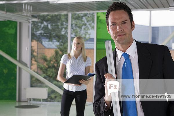 Selbstbewusster Geschäftsmann mit Frau im Hintergrund