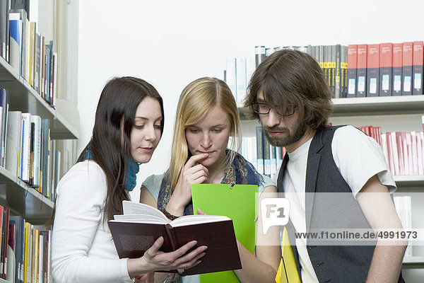 Drei Studenten in der Bibliothek