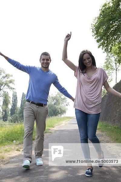 Ausgelassenes junges Paar auf einem Weg
