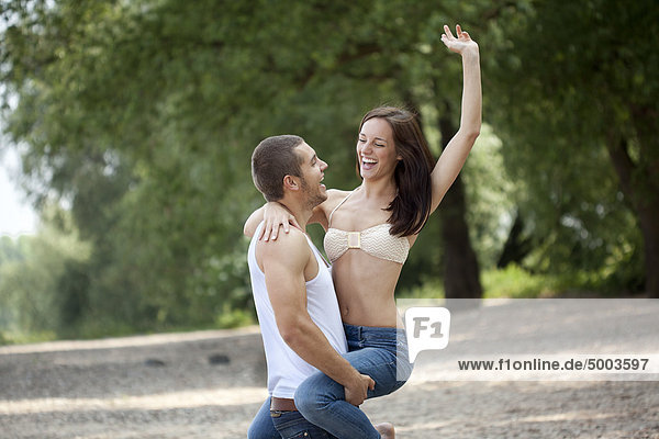 Junger Mann trägt Frau im Freien