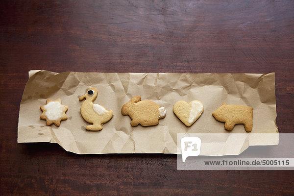 Kekse in einer Reihe auf braunem Papier angeordnet Kekse in einer Reihe auf braunem Papier angeordnet