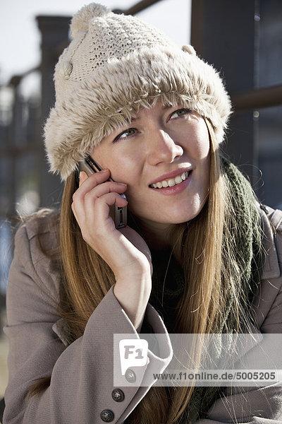 Frau draußen am Telefon