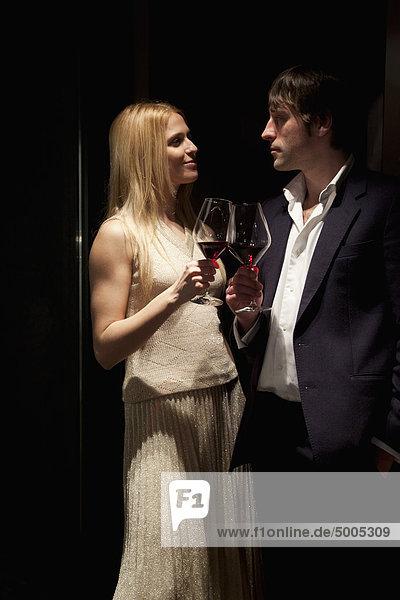 Ein Paar macht einen Toast mit Rotwein.