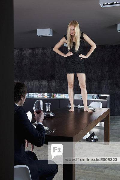 Freundin steht unzufrieden mit ihrem Freund auf dem Esstisch.