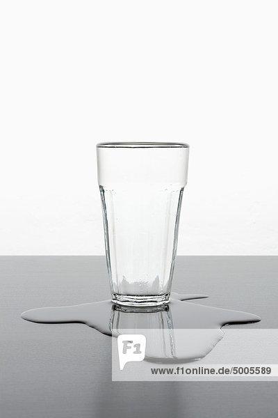 Ein aufrechtes Glas  das in einer Pfütze mit verschüttetem Wasser steht.