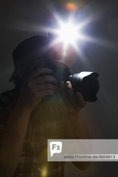 Ein Fotograf mit Kamera und Blitz