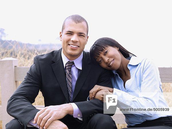 Ein Geschäftsmann und eine Geschäftsfrau  die sich gemeinsam im Freien entspannen.