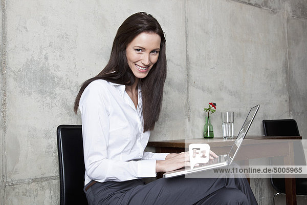 Eine Geschäftsfrau  die auf einem Laptop schreibt.