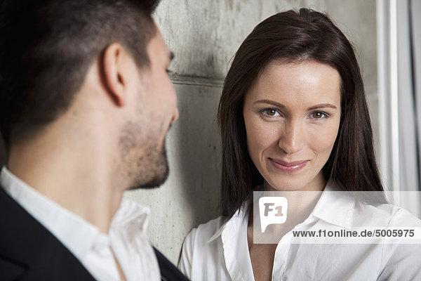 Eine lächelnde Geschäftsfrau und ein Geschäftsmann  Fokus auf Frau