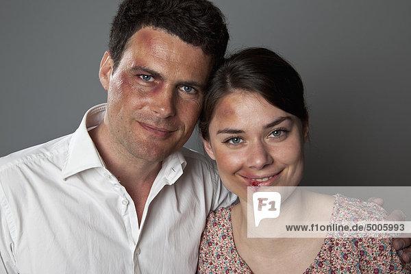Ein gequetschtes und geschlagenes Paar lächelt fröhlich in die Kamera.