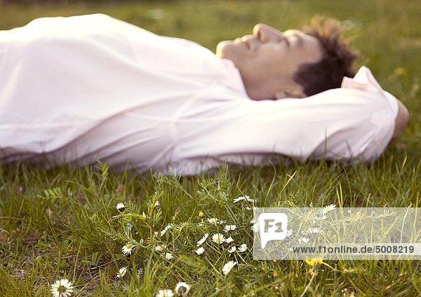 Mann liegt auf einer Wiese mit Gänseblümchen